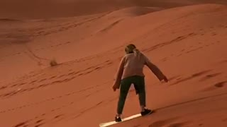 Guy rides white snowboard down sand dune and falls down