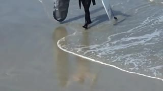 Surfer walks with his  surfboard and silver surfboard cover  - Video
