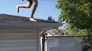 Man in striped shorts jumps from roof to white pool floatie