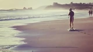 Man in black dragging surfboard on beach - Video
