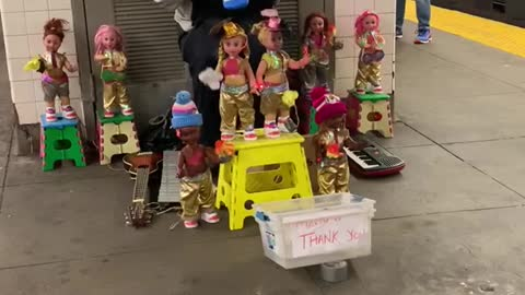 Man plays old mcdonald on blue melodica with dozens of dancing puppet dolls around him