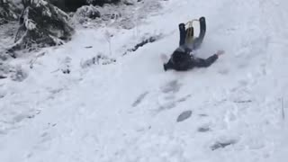 Guy goes sledding down slope on yellow sled and flies off