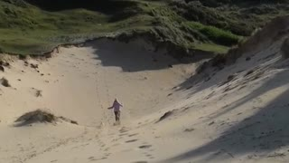 Blue shirt lady running down sand dune hill faceplants - Video