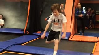 Boy in grey shirt does flip on orange trampoline, falls on head
