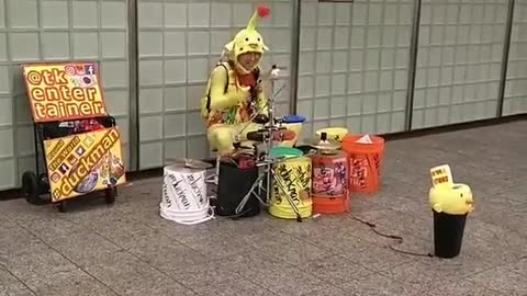 Person dressed up as alien yellow red antenna playing drums