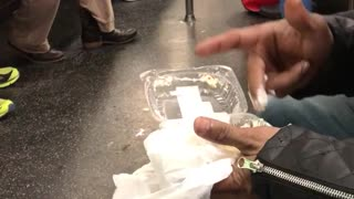 Guy in black jacket eating food with fingers on subway