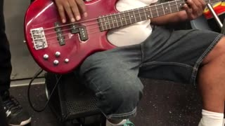 Man hanging from subway plays red guitar