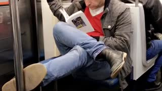Cross legged man on subway reads book - Video