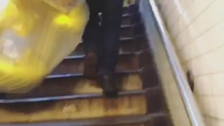 Man carrying balloons in bags through subway