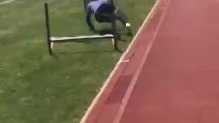 Blue shirt girl tries to jump hurdle on grass near track - Video