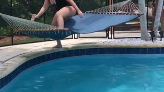 Woman Trying to Relax Flips in Poolside Hammock
