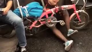 Woman with mask and pink bike pretending to ride on floor