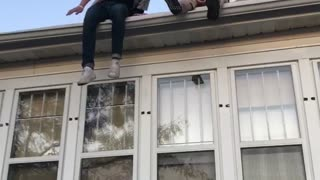 Guy jumps off small roof legs collapse - Video
