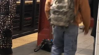 Man charging next to red pole in subway
