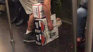 A guy in red shirt hat trying to carry beer - Video