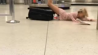 Girl in airport balancing on luggage falls on stomach - Video