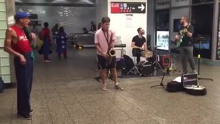 Guy in pink shirt plays saxophone in a subway station - Video