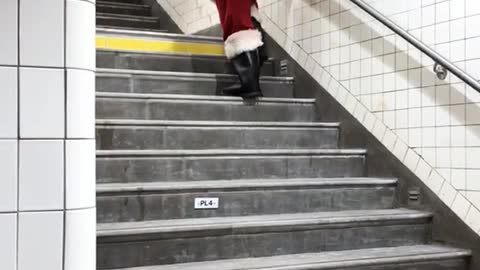 Person dressed as old santa walking up stairs slowly