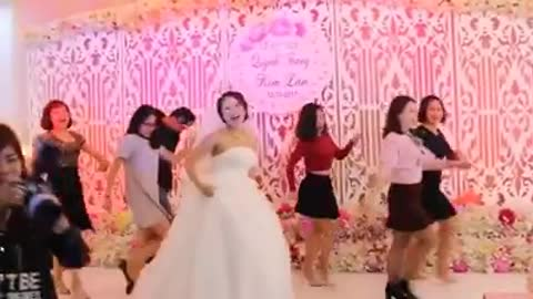 Bride with friends dancing jubilantly in her wedding