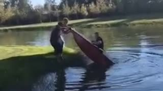 Two guys flip friend inside of red boat into lake - Video