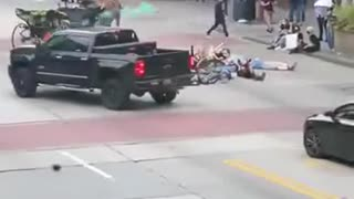 Man tosses smoke grenade into group protestors, brandishes firearm after they attack his truck