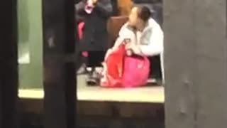 Little girl blows a toy kazoo at subway station