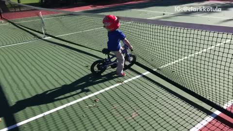 Boy riding bike runs into tennis net