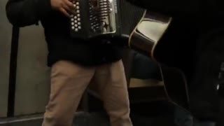 Guy on subway plays accordion and gives thumbs up to camera - Video