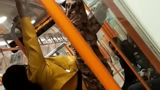 Yellow jacket woman hangs from subway poles - Video