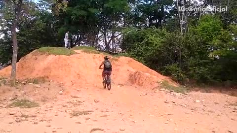 Guy tries to ride bike up of dirt hill mountain fails and falls backwards