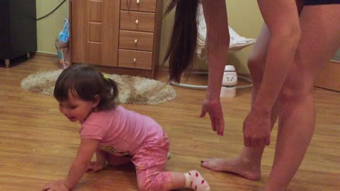 The little sister laughs funny at her older sister, when her mom stretches out