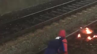 Guy on train subway tracks spiderman costume fire grill security tackle