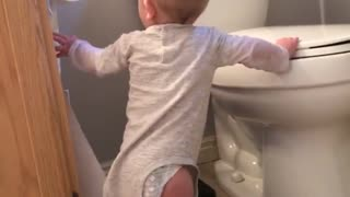 Baby pulling out roll of toilet paper, loses balance and face hits toilet