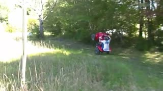 Helmet guy wheelies red four wheeler in grass and falls off - Video