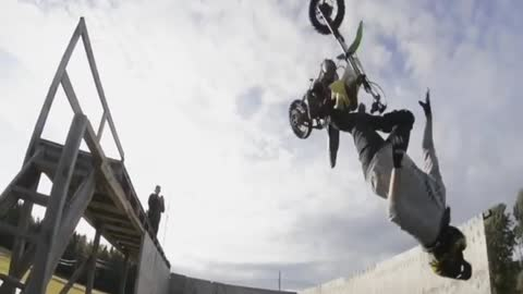 Guy motorcycle dirt bike back flip into foam pit almost gets hit by bike