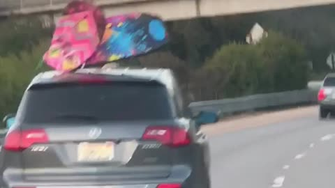 Blue and pink boogie boards on roof of car