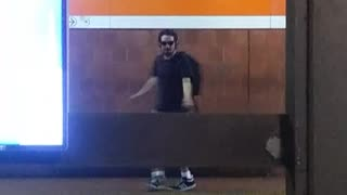 Guy dancing sunglasses headphones across subway station platforms