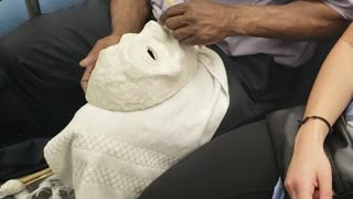 Man on subway train carving a white mask - Video
