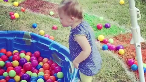 Little toddler dives into a pool full of rainbow colored balls!