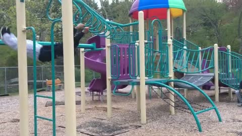 Guy tries to do a reverse backflip on monkey bars at a park.