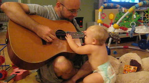Baby Rocks Out While Dad Plays The Guitar