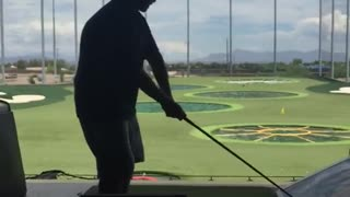 Golfer tries happy gilmore swing from second level of driving range and falls over edge - Video