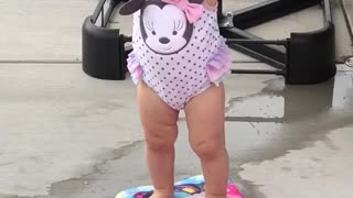 Small girl pink bathing suit stands on boogie board - Video