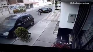 Surveillance camera man falls forward off bike between cars - Video