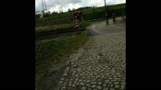 Another extremely near miss at a train crossing in the Tour of Flanders bike race. - Video