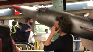 Man carrying large fake missile through subway