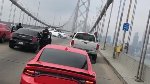 Cars block bridge while dangerously making doughnuts