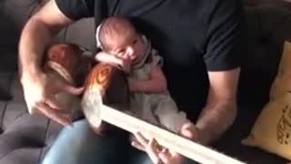 2-week-old baby relaxes while dad jams soothing music