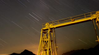 Beautiful moving star trail over mountains and metal structure.