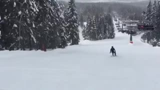 Snowboarder purple jacket falls backwards on hill - Video